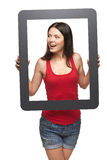 Excited teen girl looking through frame. Excited teen girl looking to the side through frame, over white background Stock Photography
