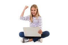 excited teen girl sitting on the floor, celebrating success with one arm raised,isolated Royalty Free Stock Image