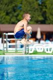 Excited teenage boy jumping in pool stock photos
