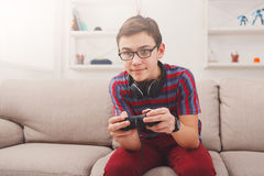 Excited teenage boy playing video game at home Stock Images