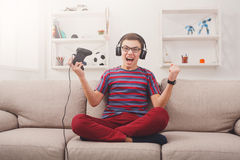 Excited teenage boy playing video game at home Royalty Free Stock Image
