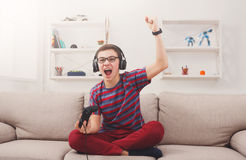 Excited teenage boy playing video game at home Royalty Free Stock Photo