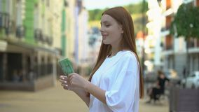 Excited teenage girl holding euro banknotes standing on street, first salary stock video footage