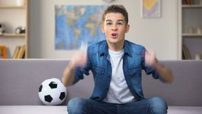 Excited teenage student watching football match on TV cheering for national team. Stock footage stock footage