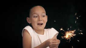 Excited teenager girl holding in hands bright sparkler on black background stock video