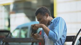 Excited teenager playing action game on smartphone sitting on bench, addiction. Stock footage stock video footage