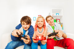 Excited teens hold joysticks and play game console. Sitting on the sofa at home Stock Photo