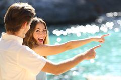 Excited teens pointing beach on vacation stock photos