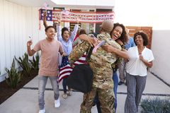 Excited three generation African American  family embracing millennial soldier returning home to them. Excited three generation black family embracing millennial royalty free stock photos