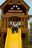 Excited Toddler Sitting in a Tree House ready to S. Photo of an Excited Toddler Sitting in a Tree House ready to Slide royalty free stock photo