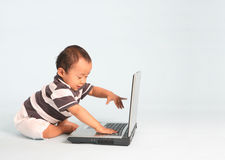 Excited Toddler Using a Laptop. An Excited toddler using a laptop computer Stock Images