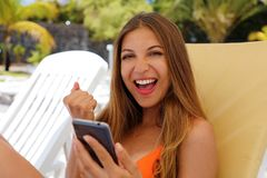 Excited tourist checking smart phone and looking at camera celebrating on summer vacation at resort on the beach.  royalty free stock image