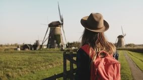 Excited tourist woman waves arms near a windmill. Traveler girl in hat with red backpack enjoys rustic mill scenery. 4K. Excited tourist woman waves arms near a stock video footage