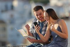Excited tourists finding best offer on a smart phone. Sitting on a ledge in a town royalty free stock photo
