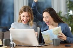 Excited tourists finding online offer at hotel room. Two excited tourists finding online offer in a laptop at hotel room or apartment stock images