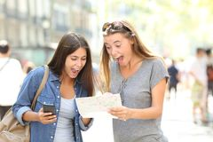 Excited tourists traveling finding location in a guide. Two excited tourists traveling finding location in a paper guide in the street Royalty Free Stock Images
