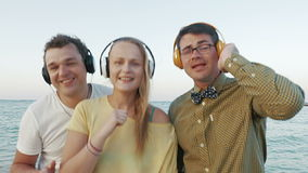Excited trio enjoying music in headphones outdoor. Two young men and woman dancing with music by the sea. Happy people listening favorite rhythms in headphones stock footage