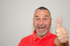 Excited triumphant man giving a thumbs up. Excited triumphant man in red shirt giving a thumbs up gesture with his hand signalling his jubilation at good news royalty free stock image