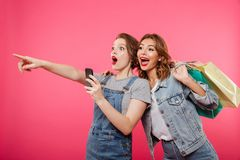 Excited two women friends holding shopping bags using mobile phone. Stock Photo