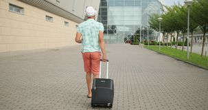 Excited unknown african man is ready for holiday. He is pulling his suitcase to the airport. 4k. Rear view. Excited unknown african man is ready for holiday. He stock footage