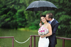 An excited wedding couple in a rainy day Royalty Free Stock Photography