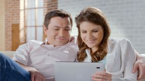 Excited wife and husband looking at tablet, shopping online, family business Royalty Free Stock Image