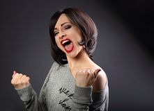 Excited winner makeup short hair style woman with opened mouth. Happy young satisfacted female showing the gesture yes by fists on grey dark background Stock Photography