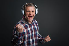Excited witty man loving the new track. Power of music. Inspired active nice guy being very emotional while listening to some music and having his headphones on Stock Images
