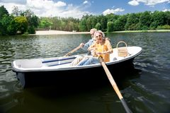 Aged woman feeling excited while holding paddle sitting in boat. Excited woman. Aged beautiful fashionable women feeling extremely excited while holding paddle stock photography