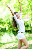 Excited Woman With Arms Raised Standing In Park Stock Photo