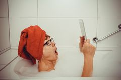 Excited woman in bathtub with tablet computers. Close up stock photos