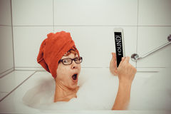 Excited woman in bathtub with tablet computers Stock Photo