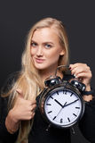 Excited woman with big alarm clock gesturing OK Stock Images
