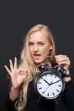 Excited woman with big alarm clock gesturing OK Royalty Free Stock Photography