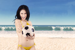 Excited woman in bikini holding soccer ball 1. Portrait of sexy woman wearing bikini holding a soccer ball on beach Royalty Free Stock Photography