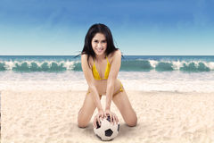 Excited woman in bikini holding soccer ball. Portrait of sexy woman wearing bikini holding a soccer ball on beach Stock Image