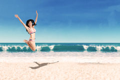 Excited woman in bikini jumping on beach Stock Photography