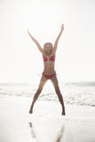 Excited woman in bikini jumping on the beach Stock Image