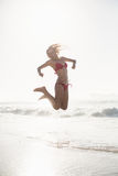 Excited woman in bikini jumping on the beach Stock Images