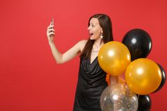 Excited woman in black dress holding air balloons doing taking selfie shot, making video call, talking on mobile phone stock photography