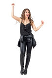 Excited woman in black leather clothes with arms raised up. Full body length portrait isolated over white studio background Stock Image