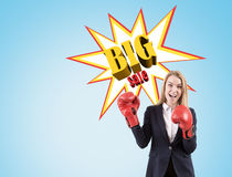 Excited woman in boxing gloves near big sale sketch on a blue wa Stock Image