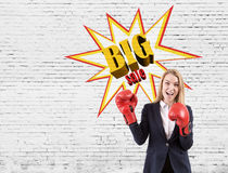 Excited woman in boxing gloves near big sale sketch on a brick w Royalty Free Stock Photos