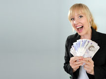 Excited woman with British currency. Excited laughing attractive blond girl with fans of British twenty pound notes stock photo