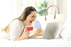 Excited woman buying online in vacations. Excited woman buying online with a credit card and a laptop on a bed of an hotel room in summer vacations Stock Images