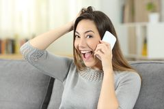 Excited woman calling on phone looking at camera. Sitting on a couch in the living room at home Royalty Free Stock Photo
