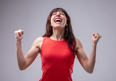 Excited woman celebrating with clenched fists royalty free stock image