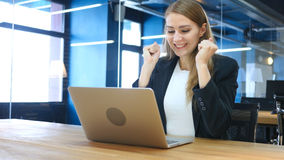 Excited Woman Celebrating Success, Working on Laptop. High quality Royalty Free Stock Photography