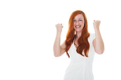 Excited woman celebrating a victory. Excited young redhead woman celebrating a victory punching the air with her fists in jubilation, upper body isolated on Royalty Free Stock Photography