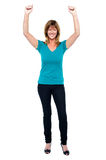 Excited woman in celebration mood with raised arms Stock Photos
